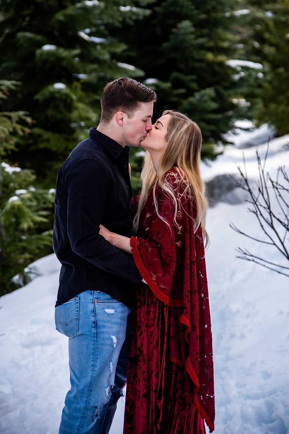 A couple kissing on their elopement day, the bride is wearing a bright red gown that contrasts beautifully against the snowy background