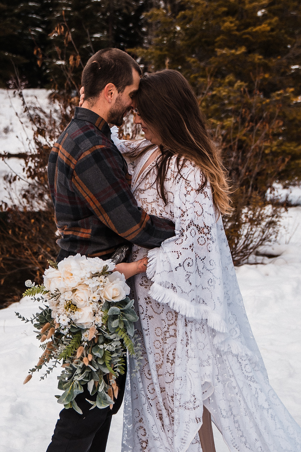 A couple snuggling in the mountains during their snowy, hiking elopement in Washington