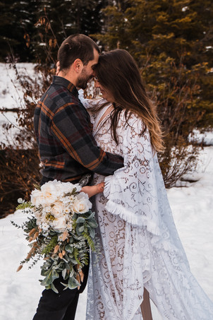 A couple touches their foreheads together and take a moment to reflect their adventures on their snowy elopement day in Washington