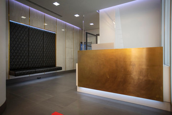 Bespoke White Corian® Reception Counter clad with Brushed Solid Brass sheet
