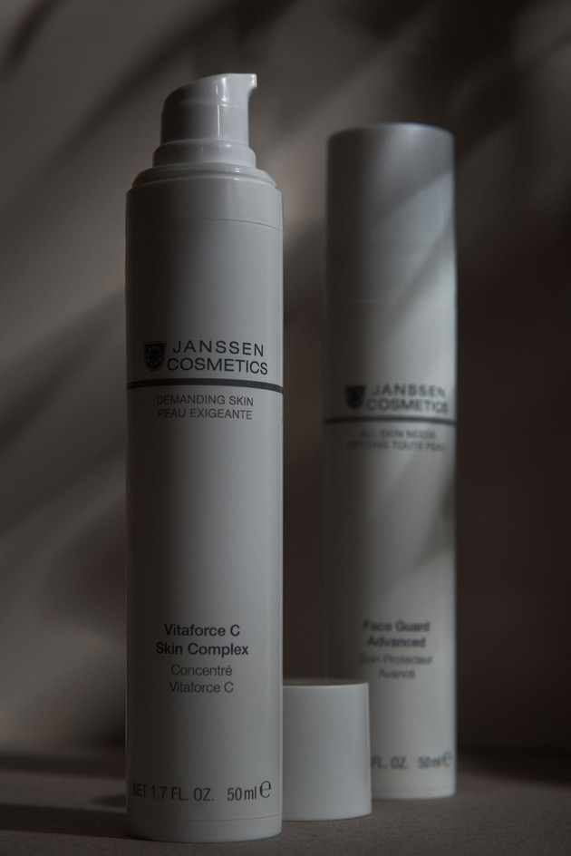 White cream tubes by Janssen Cosmetics on a white background with palm leaves shadow