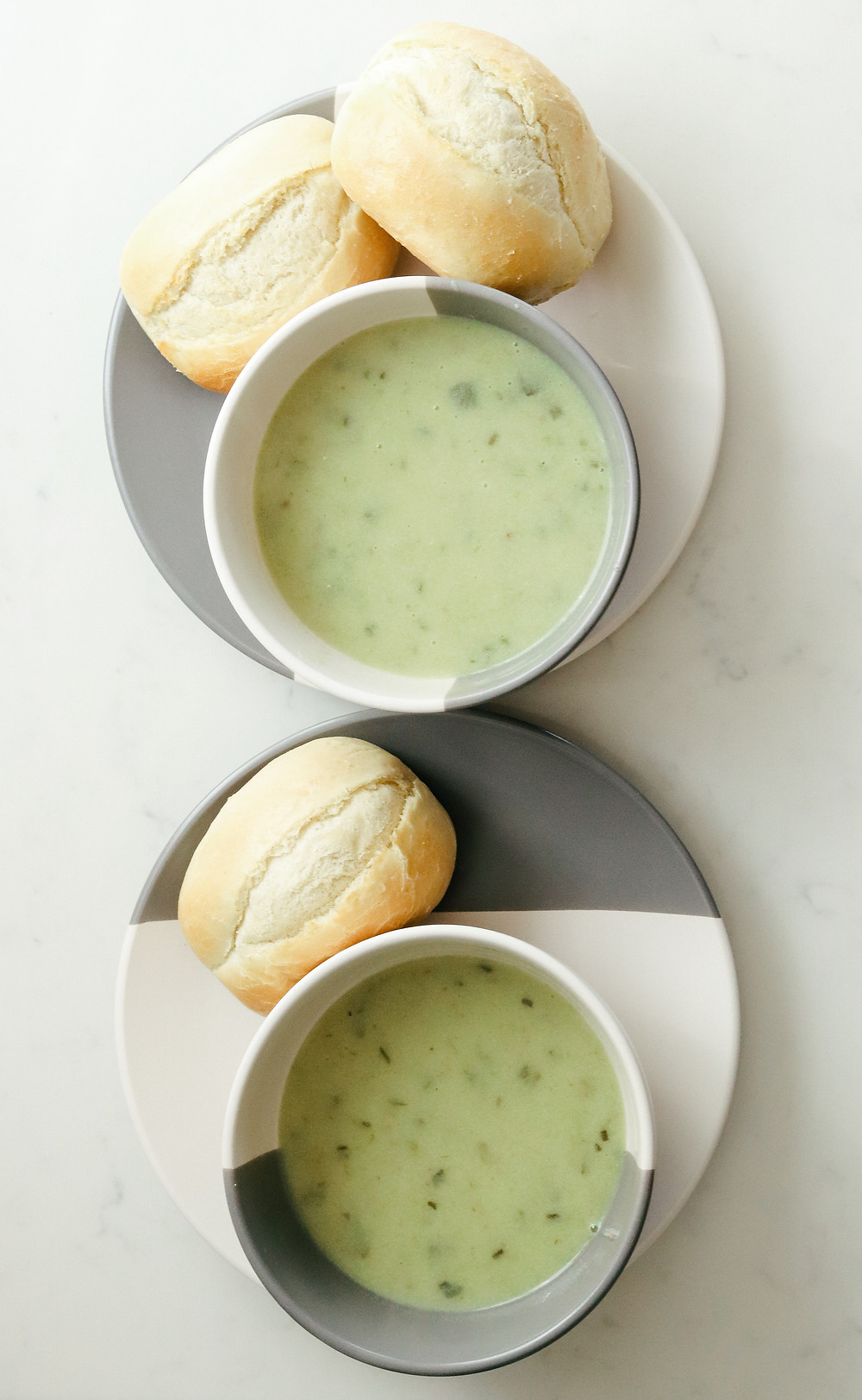 two bowls of green creamy soup and bread rolls on the plates