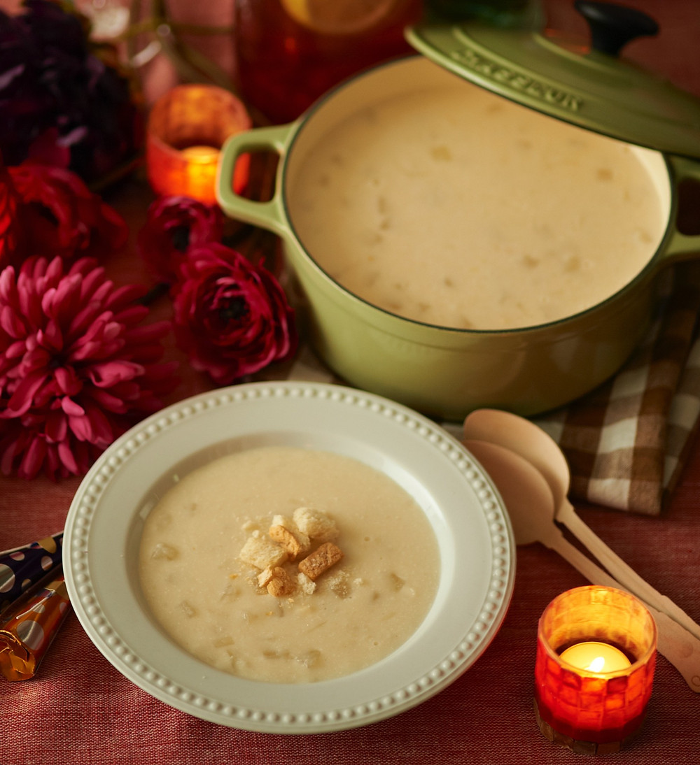 bowl of white, chunky soup with sprinkled bits, a wooden spoon, a candle, and a large, green, full pot of soup on a table