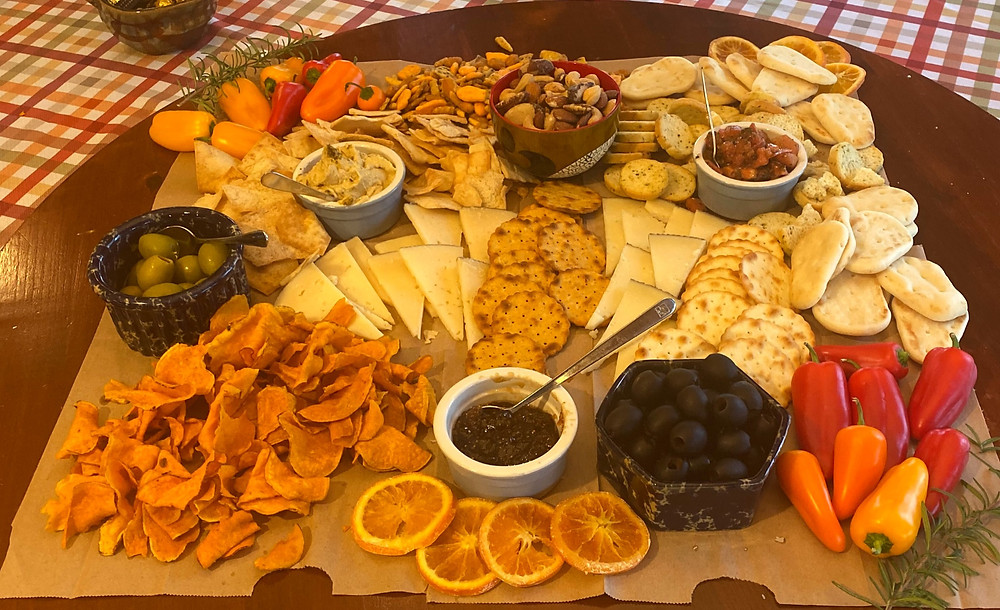 large charcuterie plate has sliced cheese, crackers, dips, olives, small sweet peppers, sliced fruits, and small bowls of nuts