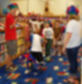 Children playing limbo in a library