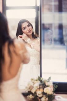 Утро невесты, невеста надевает серьги. Свадебная фотосессия для двоих в лофт квартале. Фотограф Наталия Мужецкая