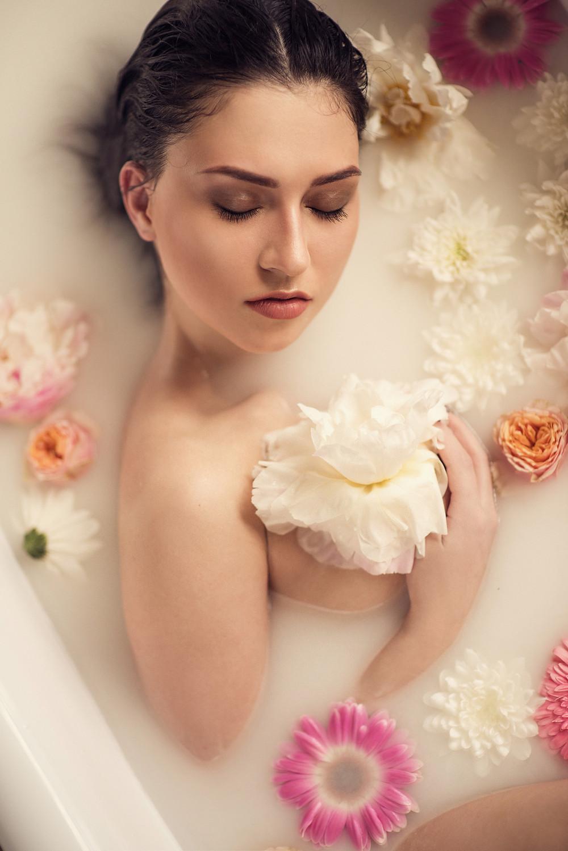 Фотосессия обнаженной модели в студии с ванной и живыми цветами