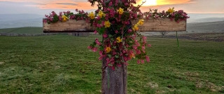 Cross with flowers at sunset