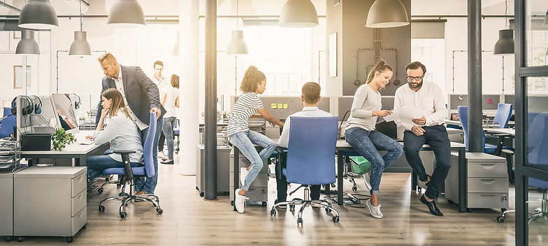 An open plan office with a mixture of staff sitting and standing around desks