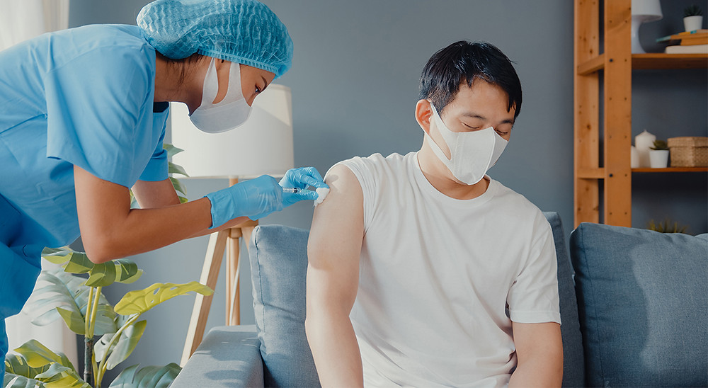 Man getting vaccinated by a nurse with the COVID-19 Vaccine