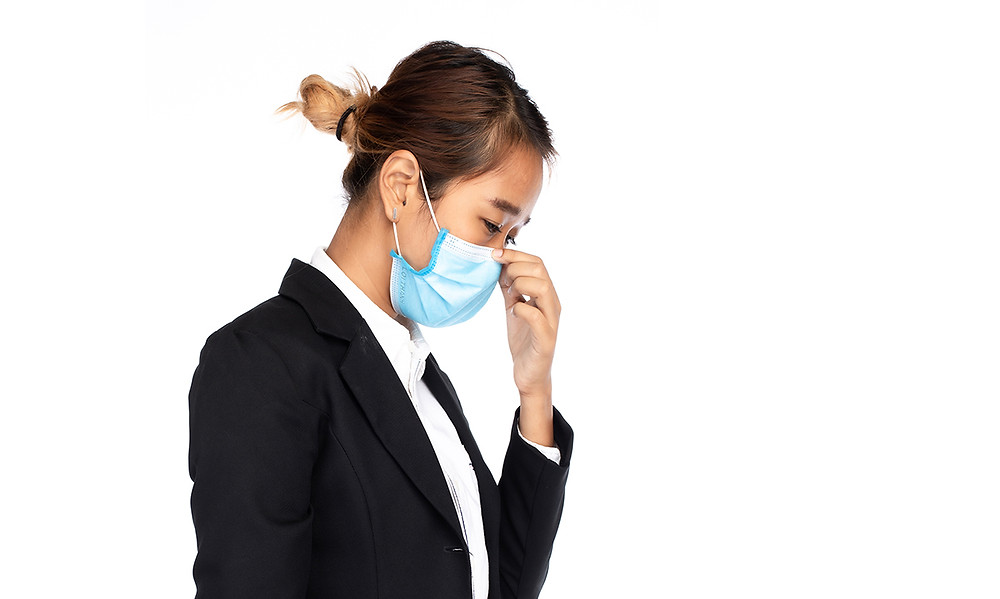 A woman pinching the tip of her face mask to fix it in place
