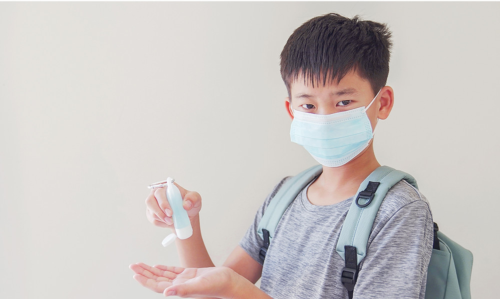 Kid using a hand sanitizer spray to clean the palm of his hand