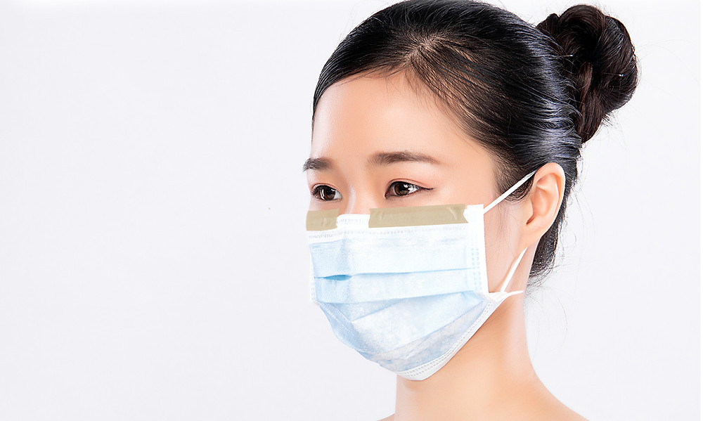 Taping down face mask to prevent breath from fogging glasses