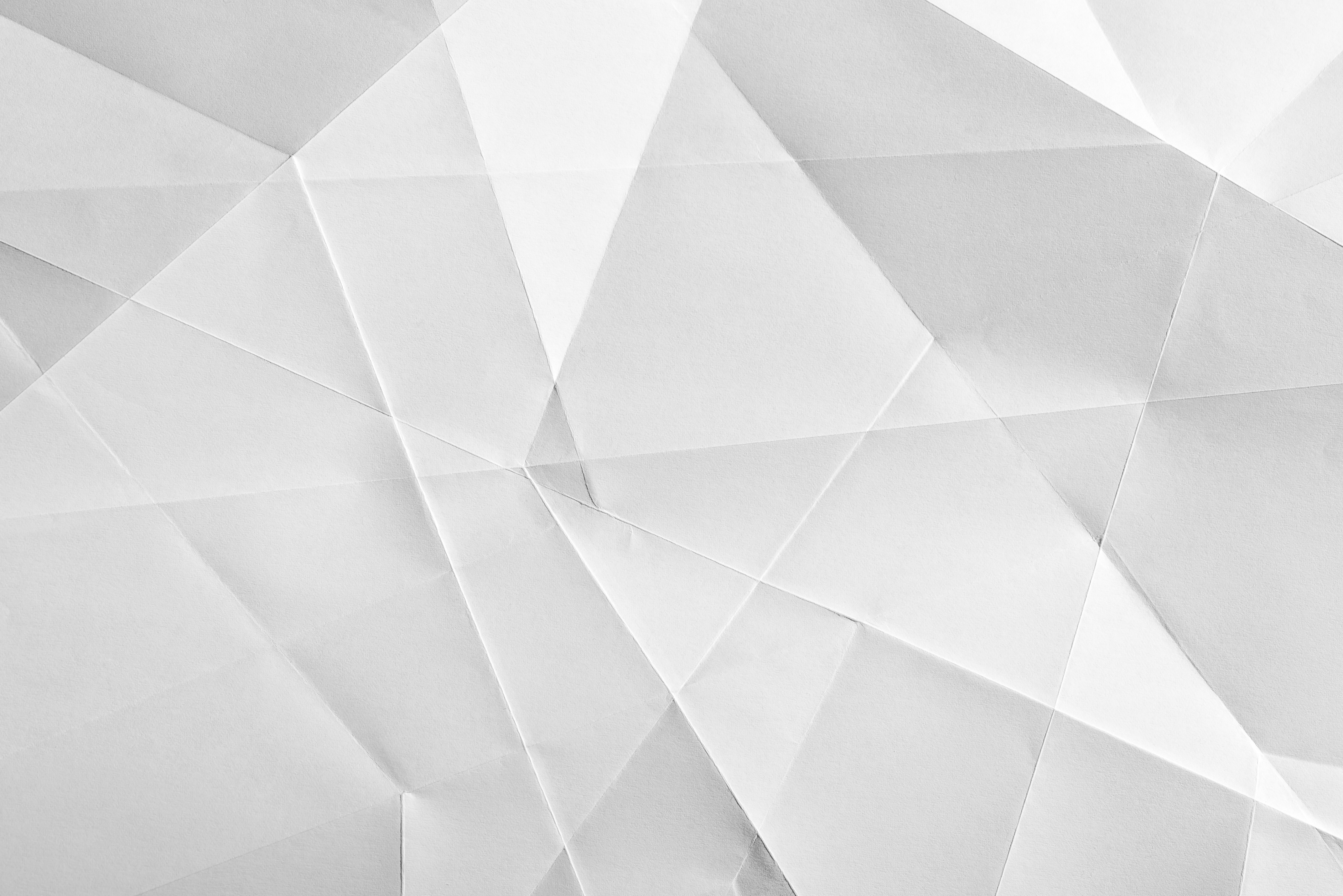 White folded sheet of paper showing an abstract texture design under the light grazing