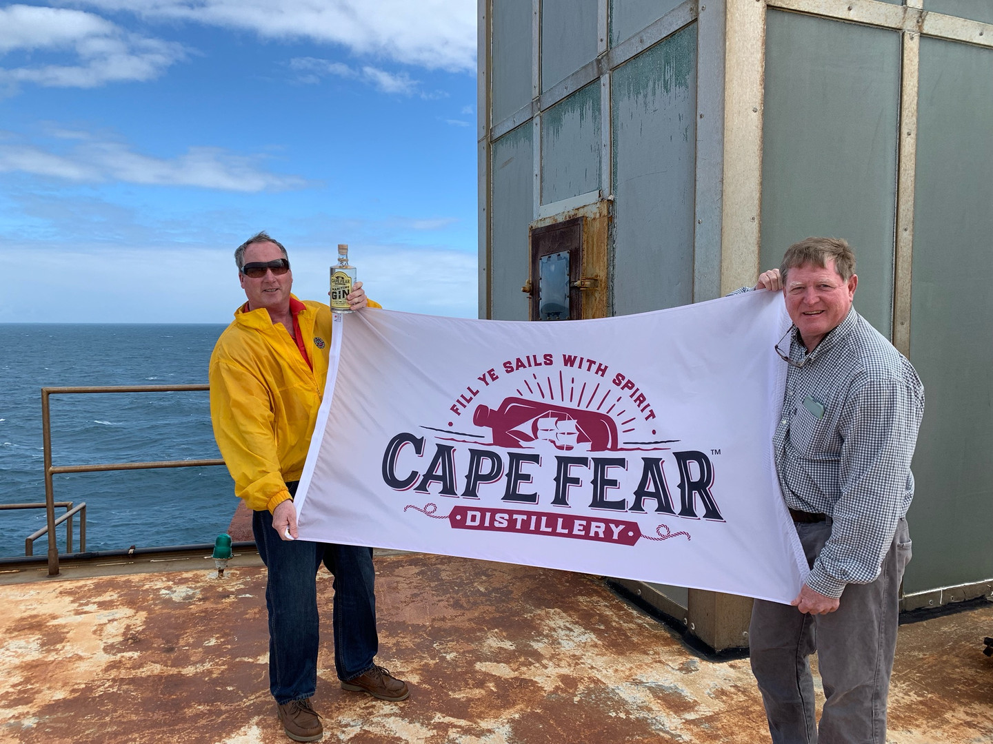 Alex and Rick flying Cape Fear Distillery Flag at Frying Pan Tower