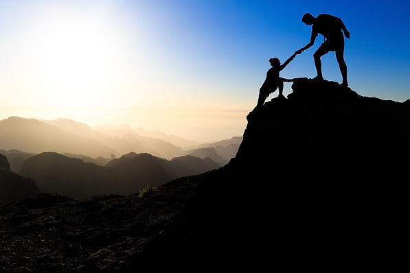 Athletes helping each other climb to mountain top