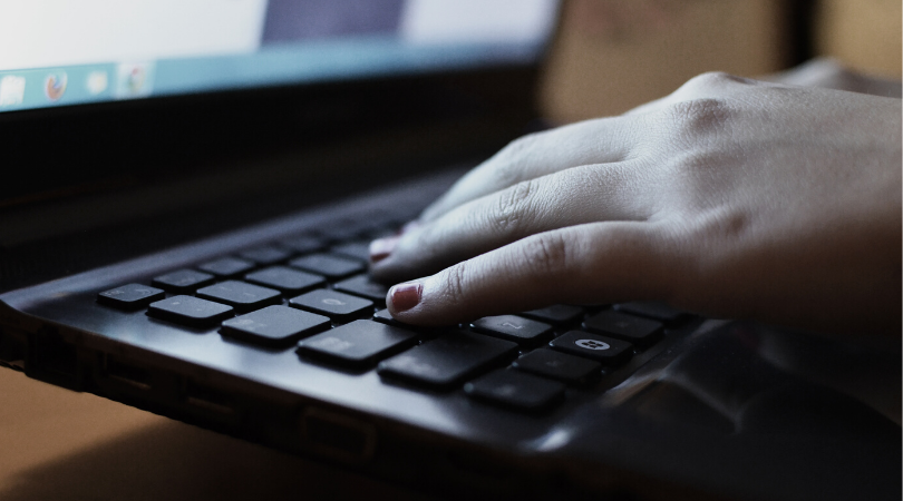 Woman's hand on keyboard of laptop