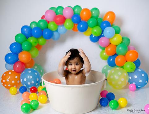 boy cake smash session ideas kids photography one year old onesie beautiful first birthday boy baby bubble bath balloon bath blue balloon wall rainbow