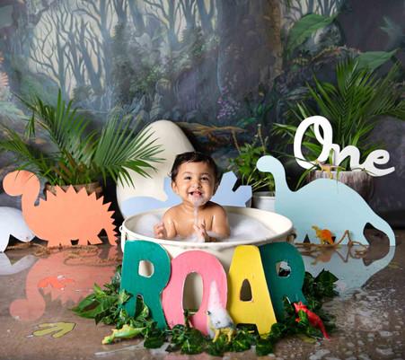 boy cake smash session ideas dino theme dinosaur jungle kids photography one year old onesie beautiful first birthday boy baby water bath