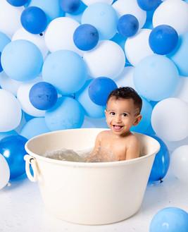 boy cake smash session ideas kids photography one year old onesie beautiful first birthday boy baby bubble bath balloon bath blue balloon wall