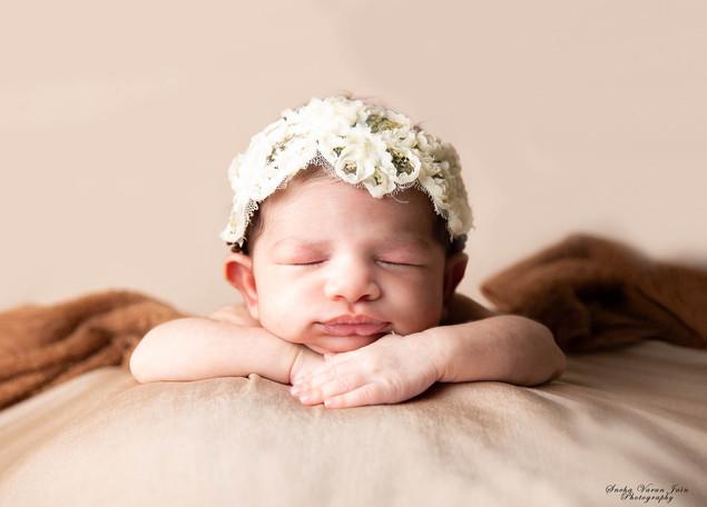 newborn photography chennai baby cute pose portrait beanbag brown hands on chin