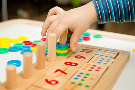 Child playing with different color wooden rings. Sequence, fine motor skills, therapy task