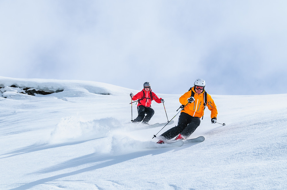 A Couple skiing downhill