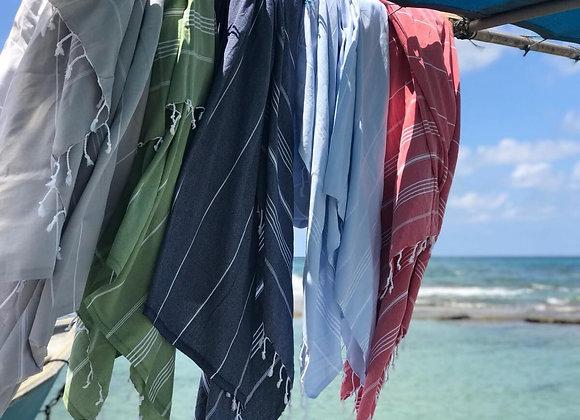 מגבות חוף תלויות על גבי עץ בחוף הים