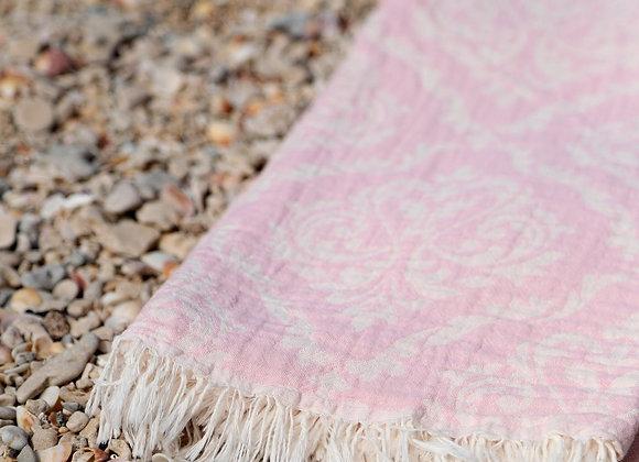 מגבת חוף בצבע ורוד פרוסה על החוף