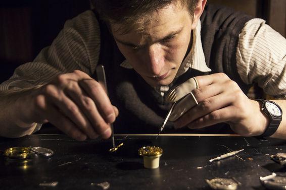The watchmaker is repairing the mechanic