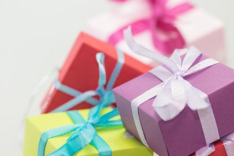 pacchi regalo colorati gialli, rossi e viola su sfondo arancione