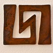 Metal art piece titled Symmetry based on a petroglyph