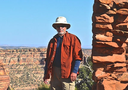 Brian Bystedt from Rendition Arts, LLC standing with ancient rocks next to and in back of him