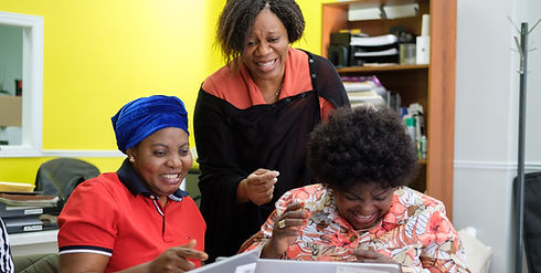 Women smiling and laughing as they look at laptops