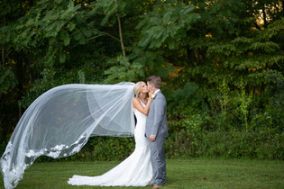 Couple Kissing in field with Veil flying.JPG