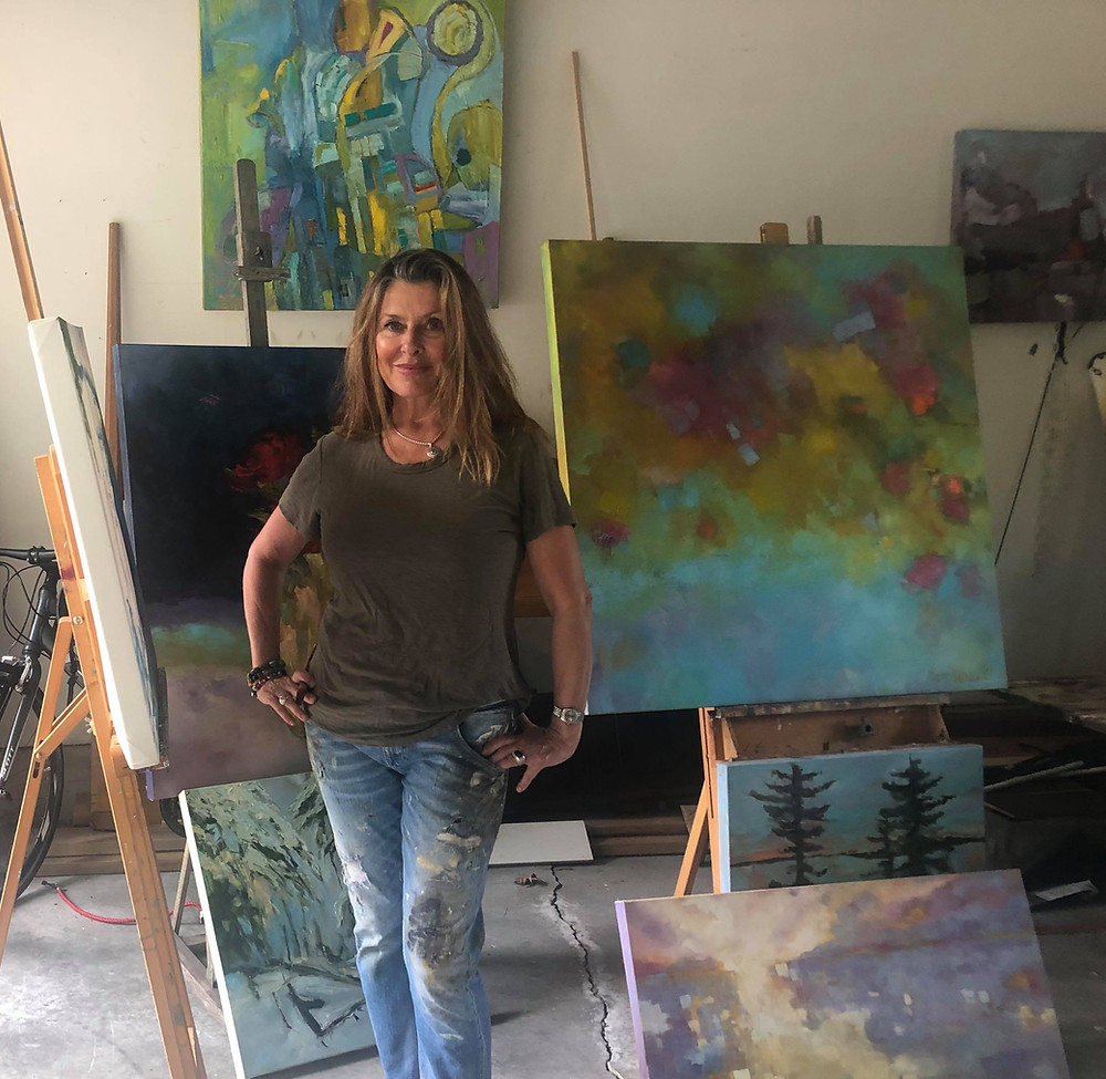 Erin Thibeault standing in her studio with a collection of her landscape art inspired by the nature of the Gatineau Hills