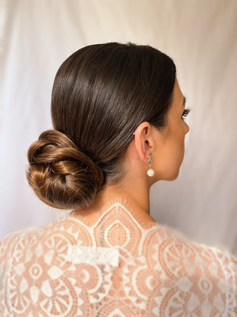 Sleek low bun with Chanel earrings