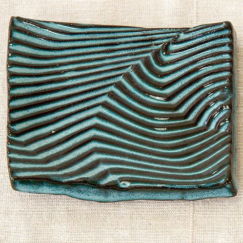 צלחת לסבון בצבע כחול מבריק על חמר שחור