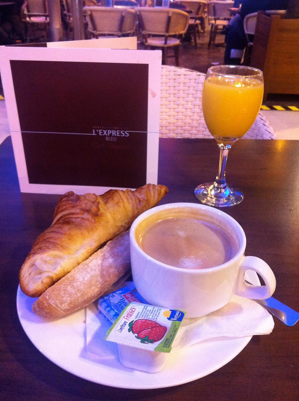 Typical breakfast in France - juice, vienoisserie, bread, jam  and café au lait