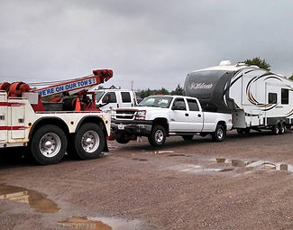 Quality Towing Services heavy-duty truck pulling white truck with fifth-wheel camper | Quality Towing Services | Clare, MI 48617