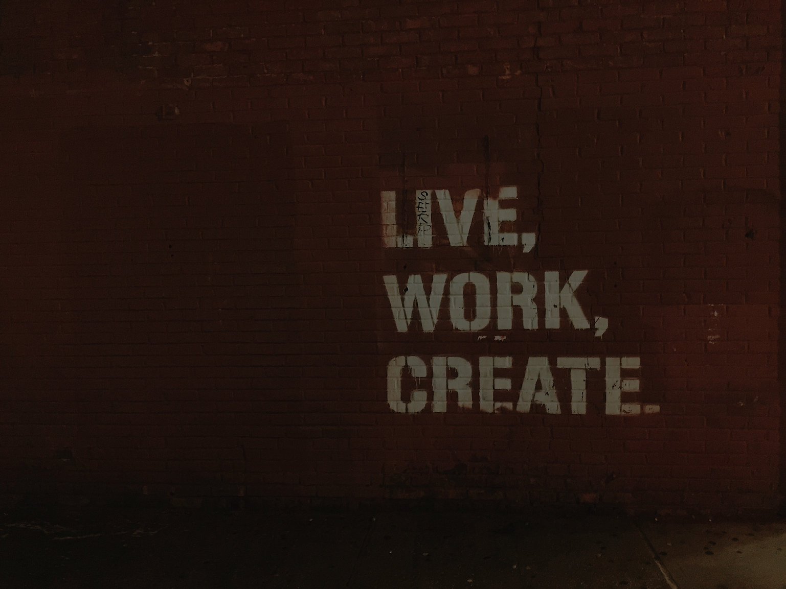 "Red brick wall with white painted words, ""Live, work, create.""  Consulting and web design."