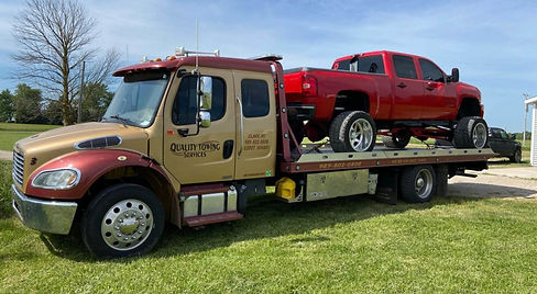 Quality Towing Services Flatbed Truck with Red Truck
