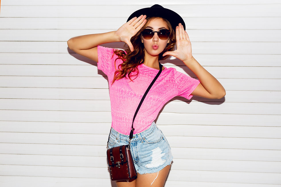 Stylish night flash fashion portrait of trendy  casual young  woman in pink neon  t-shirt