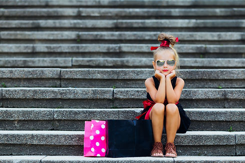 Little girl with shopping bags on street. Child with paper bags outdoor. Kid shopper in fa