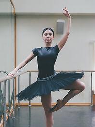 Ballerina in black tutu and pointe stret