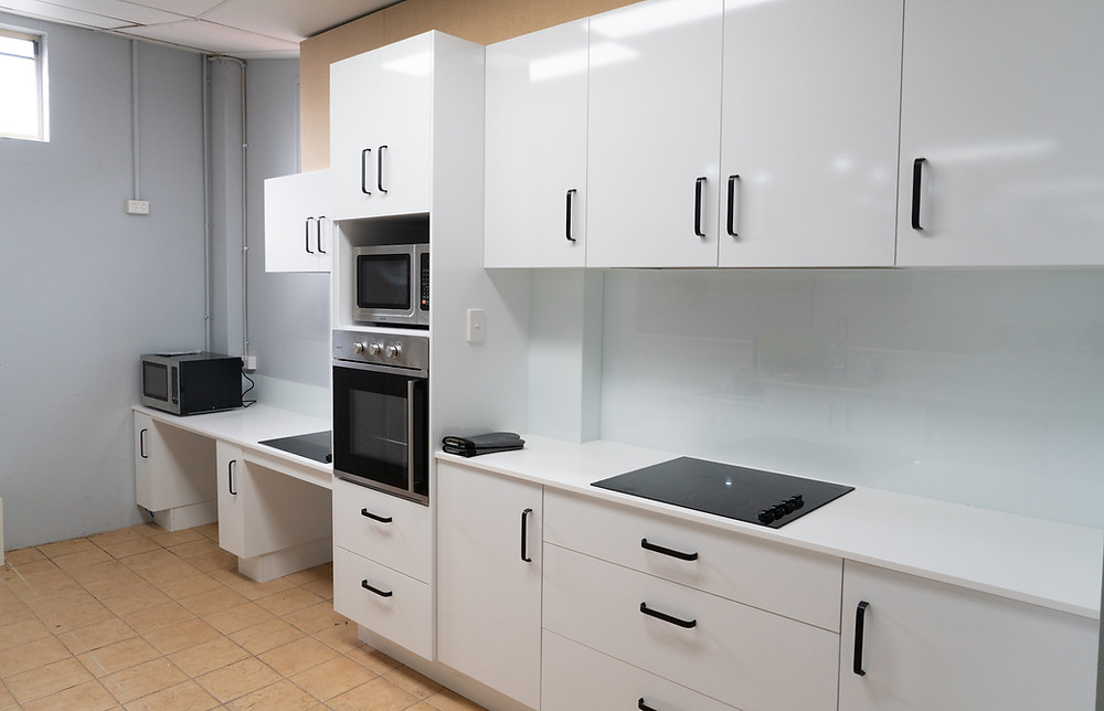 Accessible kitchen with white panels and induction oven on counter top
