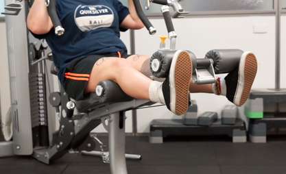 Close up of a person using gym equipment. Legs being raised from a seated position.
