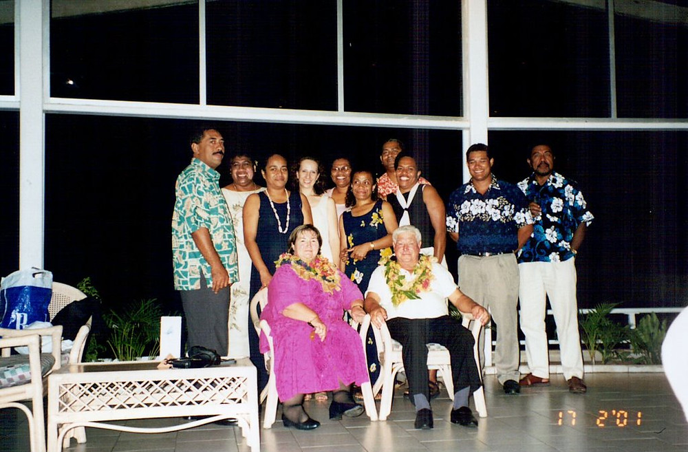 A group of people pose in a hotel foyer in Fiji. Two people in the front row are seated and wear traditional flower necklaces.