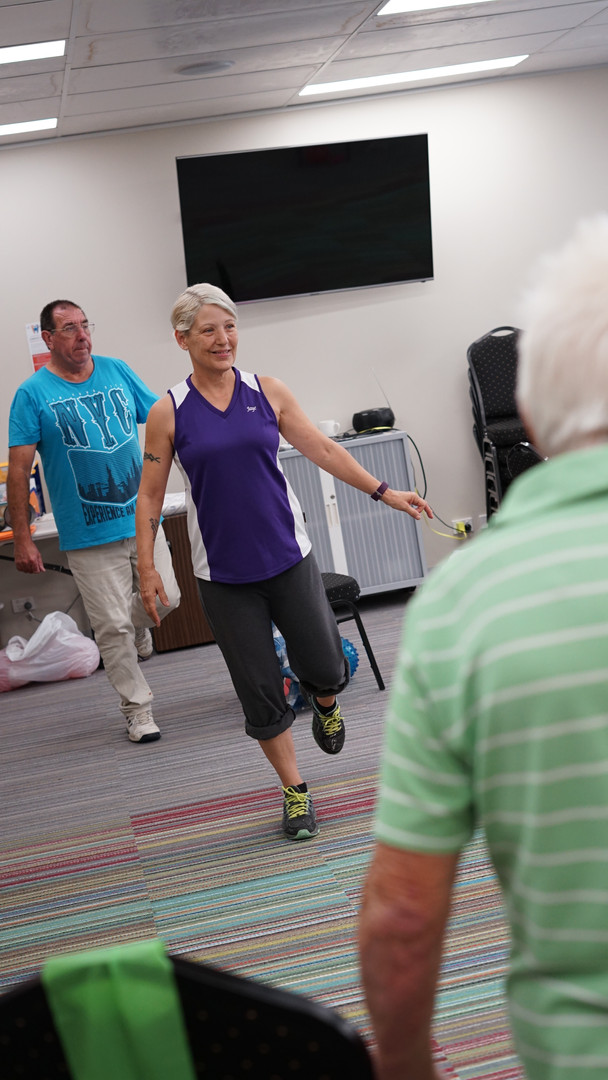 Fitness instructor balances on one leg to demonstrate movement to fitness participants