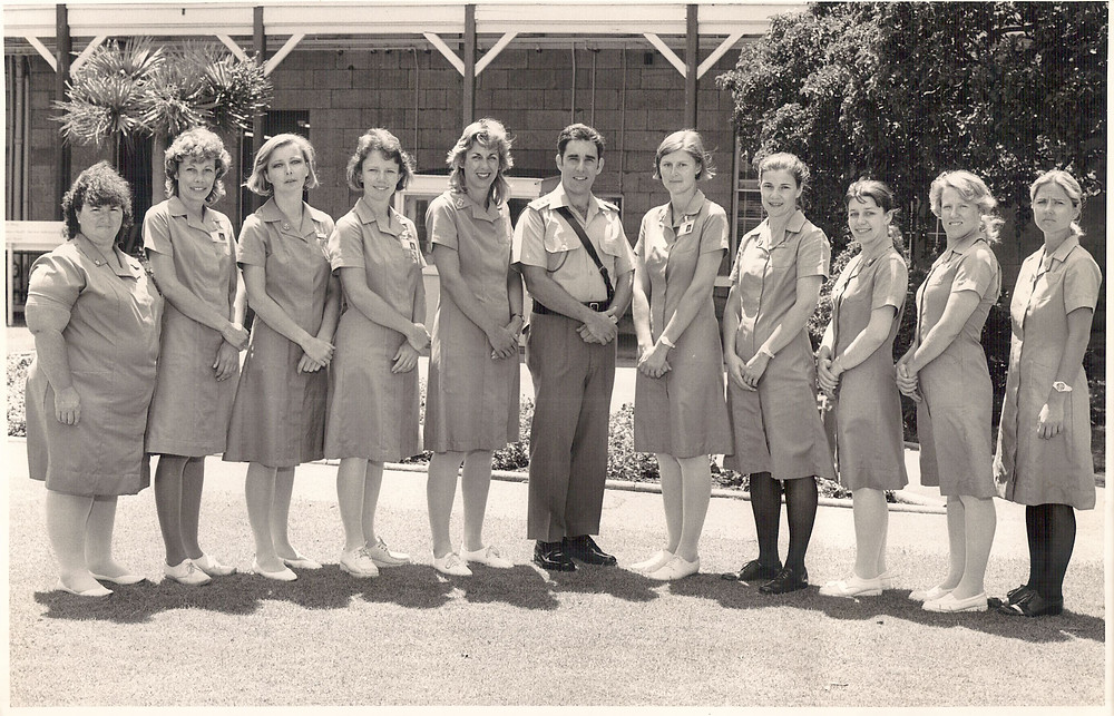 Eleven people stand in a row. The person in the middle is a man wearing a uniform, while the others are female nurses in nurse dresses.